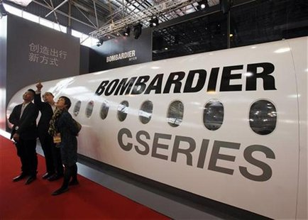 Visitors chat in front of a mock cabin of a Bombardier business jet on the first day of the China International Aviation & Aerospace Exhibit