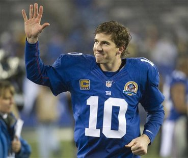 New York Giants quarterback Eli Manning waves as he runs off the field after they beat the New Orleans Saints in their NFL football game in