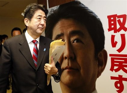 Shinzo Abe, Japan's incoming prime minister and the leader of Liberal Democratic Party (LDP), walks past his portrait after attending a meet