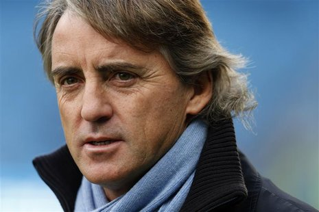 Manchester City manager Roberto Mancini walks onto the pitch before their English Premier League soccer match against Manchester United at T