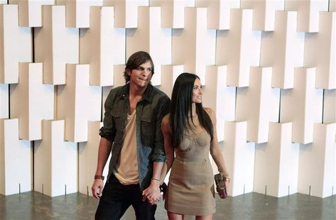 Actor Ashton Kutcher and his wife actress Demi Moore (R) arrive for Colcci's Winter 2011 collection during Sao Paulo Fashion Week January 30
