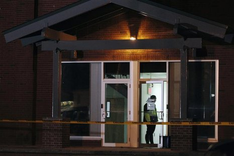 A Framingham police officer (in doorway) keeps watch as federal agents search th New England Compounding Center company in Framingham, Massa