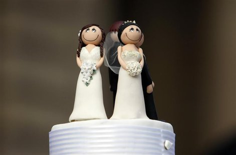 Two bride figurines adorn the top of a wedding cake during an illegal same-sex wedding ceremony in central Melbourne August 1, 2009. REUTERS