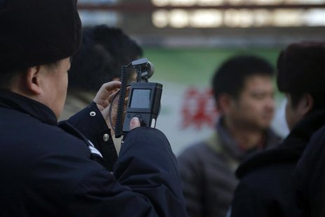 A policeman films his co-workers trying to persuade protesters from gathering near the Beijing Olympic Tower December 22, 2012. REUTERS/Peta