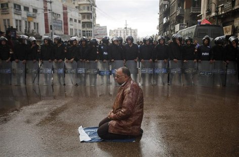 A supporter of Egyptian President Mohamed Mursi sits for prayers as riot policemen stand in line to separate pro- and anti-Mursi protesters