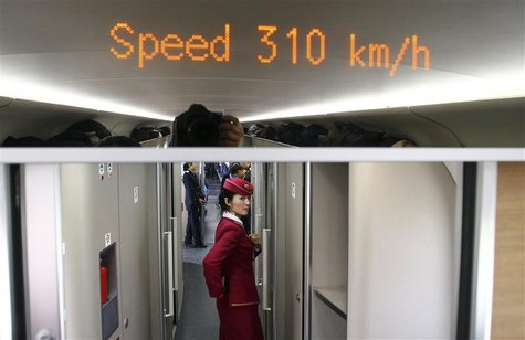 An attendant stands inside a high-speed train during an organized experience trip from Beijing to Zhengzhou, as part of a new rail line, Dec