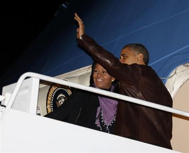 U.S. President Barack Obama waves next to first lady Michelle Obama as they prepare to depart Joint Base Andrews outside Washington, for the