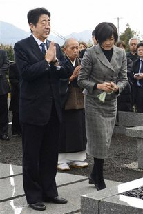 Japan's incoming Prime Minister and the leader of Liberal Democratic Party (LDP) Shinzo Abe and his wife Akie pay respects to a grave of his
