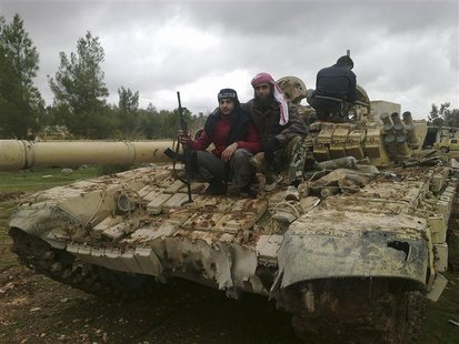 Free Syrian Army fighters pose near a tank after the fighters said they fought and defeated government troops in Al-Latameneh, near Hama Dec