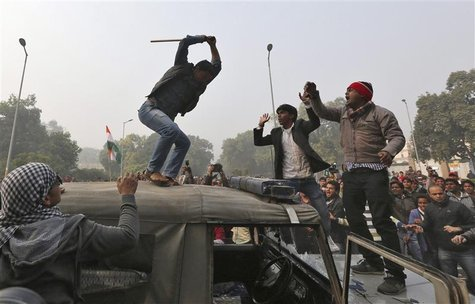 A demonstrator breaks the windshield of a police vehicle as others shout slogans in front of the India Gate during a protest in New Delhi De