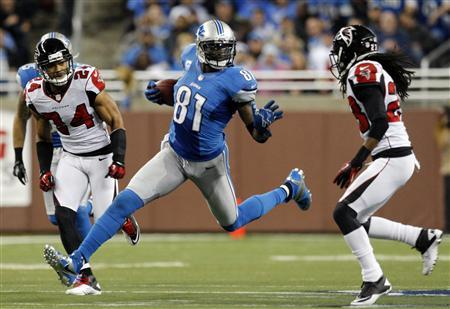 Detroit Lions wide receiver Calvin Johnson (C) carries the ball between Atlanta Falcons safety Chris Hope (L) and cornerback Dunta Robinson during the second half of their NFL football game in Detroit, Michigan December 22, 2012.  REUTERS/Rebecca Cook