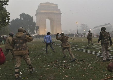 A policeman uses a baton to disperse a demonstrator during a protest in front of India Gate in New Delhi December 23, 2012. REUTERS/Ahmad Ma
