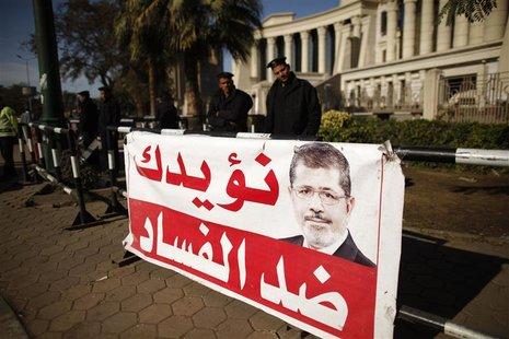 Policemen stand guard near a banner outside the constitutional court put up by supporters of Egyptian President Mohamed Mursi as they stage