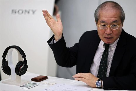 Sony China President Nobuki Kurita gestures as he gives a speech next to a Sony MDR-1R headset and a Sony mobile phone during a news confere