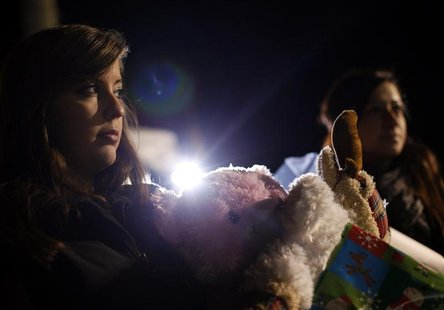 A woman holds stuff animals and Christmas presents at a memorial for the Sandy Hook Elementary School shooting victims in Newtown, Connectic