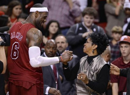 Miami Heat's LeBron James (L) is congratulated by recording artist Gladys Knight (R) following their NBA basketball game against the Oklahom