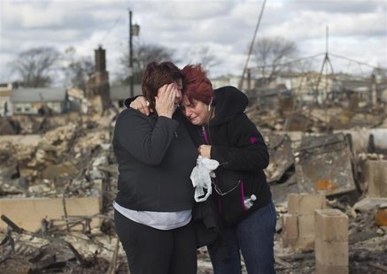 Neighbors Lucille Dwyer (R) and Linda Strong embrace after looking through the wreckage of their homes devastated by fire and the effects of