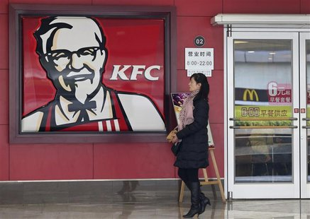 A woman walks past a KFC restaurant as a logo of McDonald is reflected on a door window, in Wuhan, Hubei province, December 18, 2012. REUTER