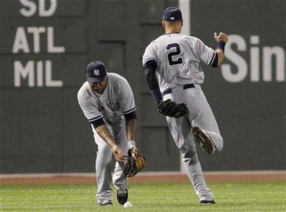 New York Yankees right fielder Andruw Jones (L) bobbles a ball hit by Boston Red Sox's Dustin Pedroia (not pictured) after Yankees teammate