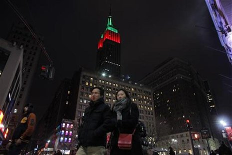 People walk near The Empire State Building as it is lit up in red and green on Christmas day in New York December 25, 2012. REUTERS/Eduardo