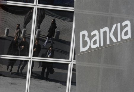 People are reflected on the windows of the headquarters of Spain's Bankia bank in Madrid November 28, 2012. REUTERS/Andrea Comas