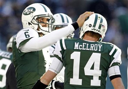 New York Jets quarterback Mark Sanchez pats quarterback Greg McElroy on the helmet after a scoring drive against the San Diego Chargers duri
