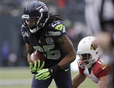 Seattle Seahawks' Richard Sherman (25) intercepts a pass meant for Arizona Cardinals' Larry Fitzgerald (11), returning it for a touchdown du