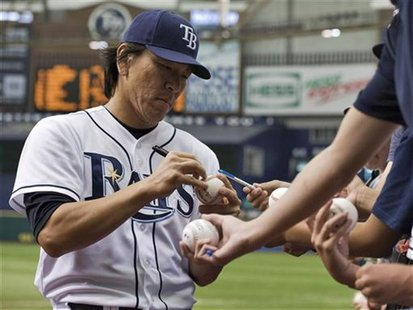 Tampa Bay Rays' Hideki Matsui signs autographs before a MLB American League baseball game against the New York Mets in St. Petersburg, Flori