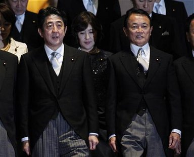 New Japanese Prime Minister Shinzo Abe (L) prepares for a photo session with Finance Minister Taro Aso and other ministers after their first