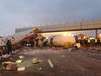 A wreckage of a plane is seen on a highway near Moscow's Vnukovo airport December 29, 2012. A Russian jet went off a runway and split into t