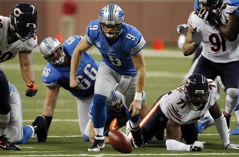 Detroit Lions quarterback Matthew Stafford (C ) chases the ball after a fumble and before Chicago Bears defensive end Julius Peppers (L ) re