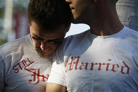 Gay couple Ethan Collings (L), 32, and his spouse Stephen Abate, 36, hug as they celebrate their one-year wedding anniversary in West Hollyw