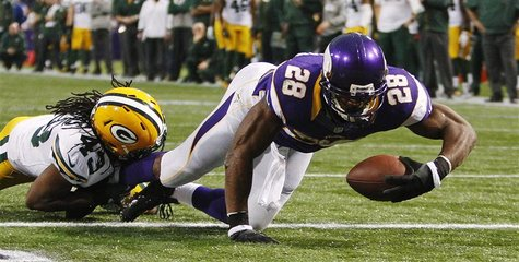Minnesota Vikings running back Adrian Peterson (28) scores a touchdown past Green Bay Packers safety M.D. Jennings on a seven-yard carry in