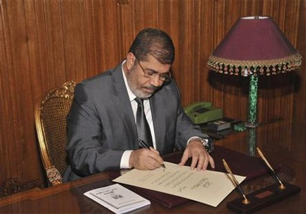 Egypt's President Mohamed Mursi signs a decree to put into effect the new constitution in Cairo December 25, 2012, in this handout photo rel