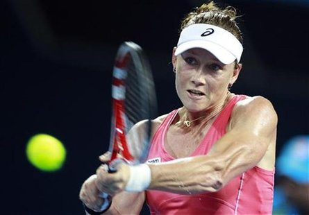 Samantha Stosur of Australia hits a return against Sofia Arvidsson of Sweden during their women's singles match at the Brisbane Internationa