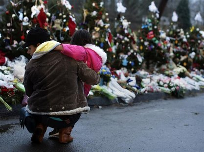 A woman holds a child next to a makeshift memorial for victims who died in the December 14 shootings at Sandy Hook Elementary School, in New
