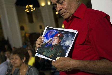 A supporter of Venezuelan President Hugo Chavez holds a picture of him, as he attends a mass to pray for Chavez's health in Caracas December
