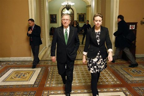 U.S. Senate Minority Leader Mitch McConnell (C) departs the senate floor with an aide after a senate vote in the early morning hours at the