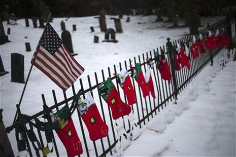 A U.S. flag hangs over stockings left as a memorial for victims of the Sandy Hook Elementary School shooting, along a fence surrounding the