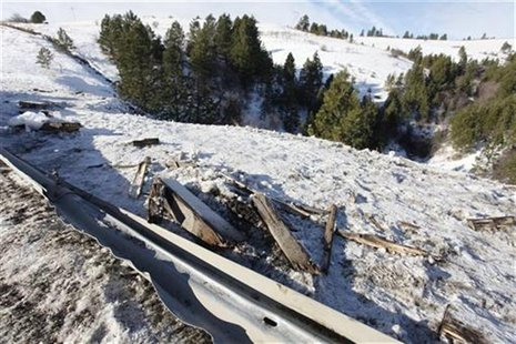Twisted guard rail and debris line road side where tour bus careened off a mountain highway and plunged down a snow-covered slope, killing n