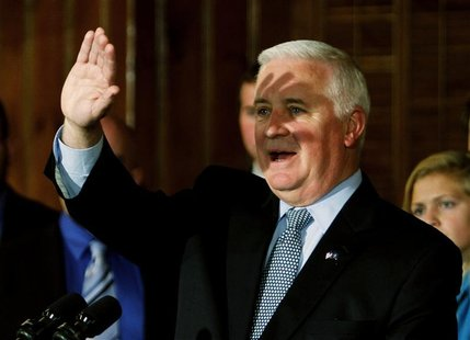 Pennsylvania Governor Tom Corbett shields his eyes during a news conference with a group of Penn State students at the Nittany Lion Inn in S