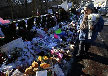 A woman with flowers walks past a makeshift memorial in Sandy Hook, after the December 14 shooting tragedy when a gunman shot dead 20 studen