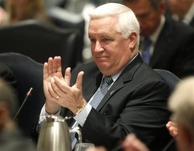 Pennsylvania Governor Tom Corbett applauds the introduction of Penn State University's interim president Rodney Erickson during the trustees