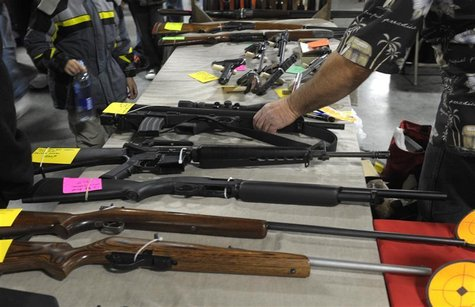 A dealer displays firearms for sale at a gun show in Kansas City, Missouri December 22, 2012. REUTERS/Dave Kaup