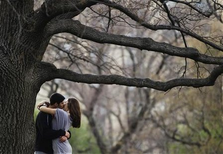 A couple kisses while standing underneath a tree inside Central Park during a warm day in New York, March 22, 2012. REUTERS/Lucas Jackson