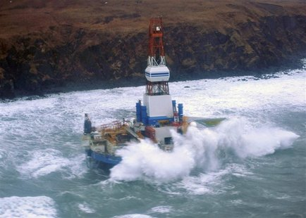 Waves crash over the conical drilling unit Kulluk where it sits aground on the southeast side of Sitkalidak Island, Alaska in this U.S. Coas