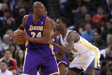 Los Angeles Lakers guard Kobe Bryant (L) looks for an opening as Golden State Warriors Harrison Barnes defends, during the first quarter of