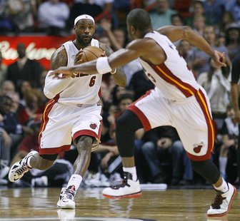Miami Heat's LeBron James (L) prepares to pass to teammate Dwyane Wade in overtime against the Dallas Mavericks during their NBA basketball