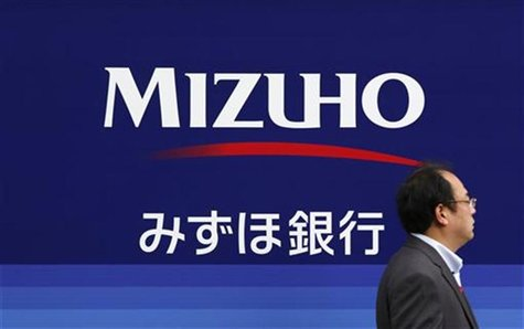 A man walks past a branch of the Mizuho Financial Group in Tokyo November 14, 2012. REUTERS/Yuriko Nakao