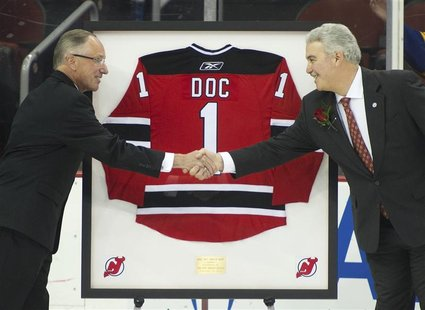 "New Jersey Devils TV announcer Mike ""Doc"" Emrick shakes hands with Devils owner Jeff Vanderbeek (R) as he is presented a framed jersey while"
